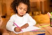 Fotografie rozkošný afroamerické kid kreslení s růžovou fixy v mateřské školce