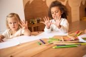 Fotografie multikulturní děti ukazuje čísla prsty ve školce