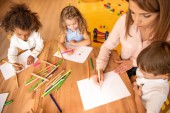 Fotografie high angle view of educator and multiethnic kids drawing in kindergarten