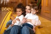 educatore che abbraccia multiculturale bambini nella scuola materna sorridenti