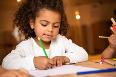 adorable african american kid erasing pencil from sheet of paper in kindergarten