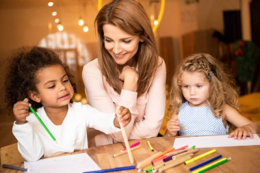smiling educator sitting near multiethnic children drawing in kindergarten