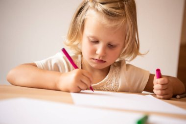 serious adorable kid drawing with pink felt pen in kindergarten