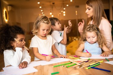 multicultural kids drawing in kindergarten, educator looking at gesturing boy