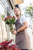 Fotografie low angle view of florist holding glass jar with burgundy roses near flower shop