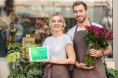 Photo happy florists holding tablet with shopping appliance and burgundy roses near flower shop