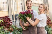 Fotografie smiling florists holding burgundy roses near flower shop and looking at camera