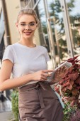 attractive florist holding tablet near flower shop and looking at camera