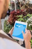 oříznutého obrazu pomocí tabletu s načtené Twitteru blízko květinářství květinářství