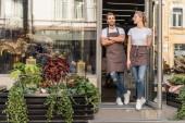 usmívající se spolupracovníky v otevřených dveří květinářství