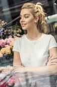 Fotografia vista attraverso la finestra di fiorista attraente in piedi con le braccia attraversate nel negozio di fiori e distogliere lo sguardo