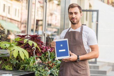 handsome florist holding tablet with loaded facebook page near flower shop