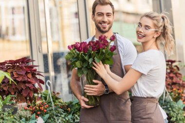 Smiling florists holding burgundy roses near flower shop and looking at camera stock vector