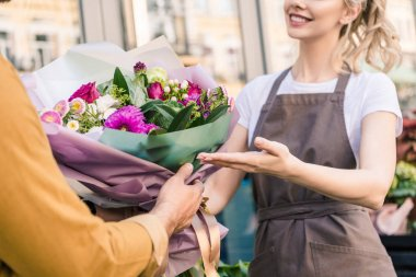 cropped image of florist giving beautiful bouquet of chrysanthemums to customer near flower shop