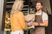 handsome florist giving wrapped bouquet to customer at flower shop