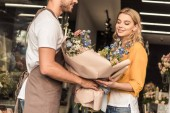 florist giving wrapped bouquet to attractive customer at flower shop