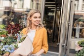 Fotografie portrait of attractive smiling girl going out from flower shop with wrapped bouquet and looking away