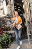 Fotografie attractive cheerful woman going out from flower shop with wrapped bouquet and looking away