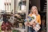 krásná žena chodit z květinářství s zalomený kytice a hledat dál