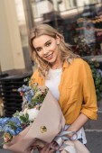 attractive girl standing with wrapped bouquet near flower shop and looking at camera