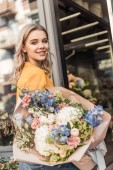 Fotografie attractive girl holding beautiful bouquet near flower shop and looking at camera