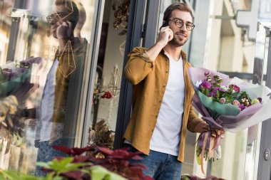 Handsome man going out from flower shop with bouquet of flowers and talking by smartphone stock vector