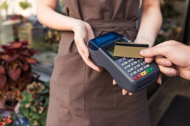 cropped image of customer paying with credit card at flower shop, florist holding payment terminal