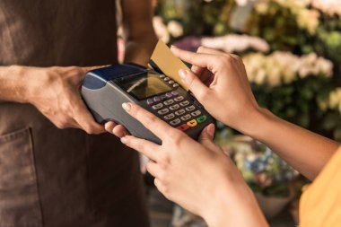 cropped image of female customer paying with credit card at flower shop, florist holding pos terminal