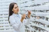 Při pohledu na brýle nedaleko poličky v oční obchodě krásné optometristy