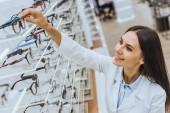 usmívající se žena optik s brýle z police v oční obchod