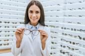 profesionální usměvavý optik drží brýle v oční obchod