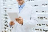ritagliata vista delloptometrista in camice bianco utilizzando la tavoletta digitale in optica