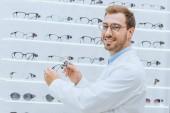 smiling doctor in white coat taking eyeglasses from shelves in optica