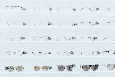 white shelves with stylish eyeglasses and sunglasses in ophthalmic shop