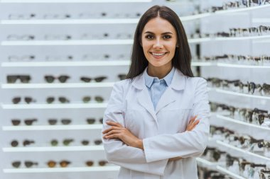professional confident optician posing with crossed arms near shelves with eyeglasses in optica