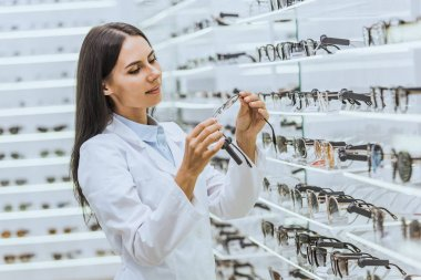 Beautiful optometrist looking at eyeglasses near shelves in ophthalmic shop stock vector