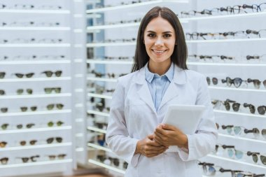 attractive professional optician with digital tablet looking at camera in ophthalmic shop