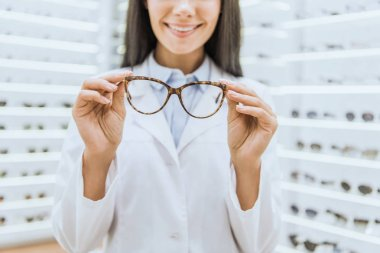 cropped view of smiling professional optometrist holding glasses