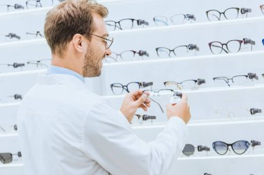 Oculist taking eyeglasses from shelves in ophthalmic shop stock vector