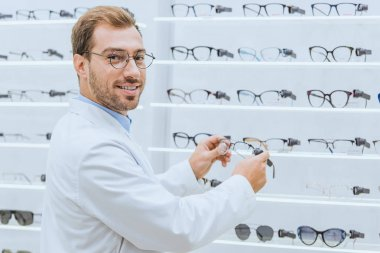 male optometrist taking glasses from shelves in ophthalmic shop