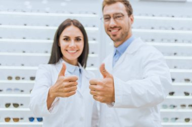 professional opticians showing thumbs up in ophthalmic shop with eyesight on shelves
