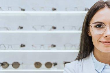 attractive female optometrist in eyeglasses standing in optica