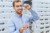 Veselý mladý muž výběru brýlí a při pohledu na fotoaparát v oční obchod