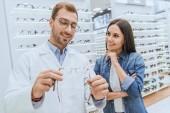 hezký mužský očnímu ukazující brýle k mladé ženě v oční obchodě