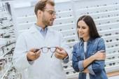 mužské optik ukazující brýle na mladé ženy v oční obchod