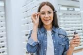 Veselá mladá žena výběr brýlí a při pohledu na fotoaparát v oční obchod