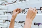 částečný pohled brát brýle z police v obchodě oční optik