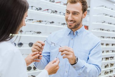 partial view of female optometrist giving eyeglasses to happy man in optics