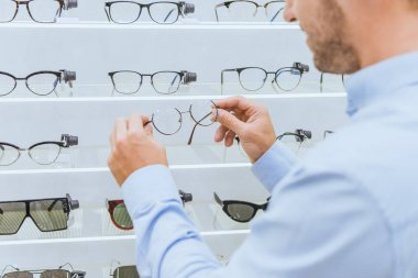 Partial view of man taking eyeglasses from shelves in optics stock vector