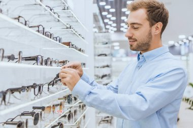 selective focus of young happy man taking eyeglasses from shelves in ophthalmic shop